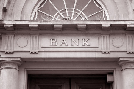 38373640 - bank sign over entrance door in black and white sepia tone